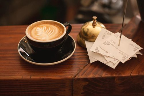 Coffee, receipts, and bell on counter top
