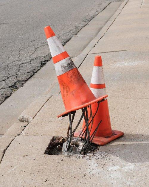 two traffic cones on hole in sidewalk