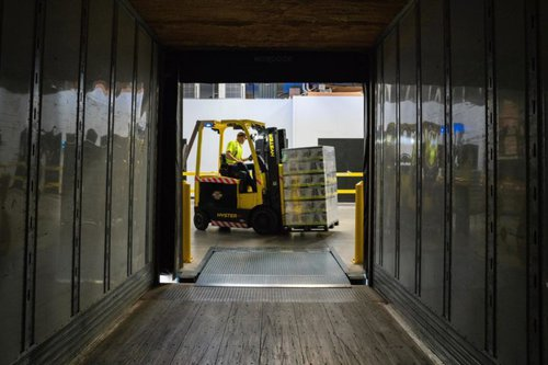 man using fork lift to move boxes