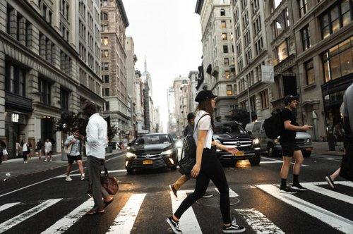 People walking on a crosswalk in a city with traffic