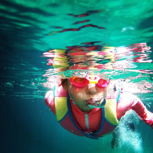 young girl wearing goggles and lifejacket while swimming