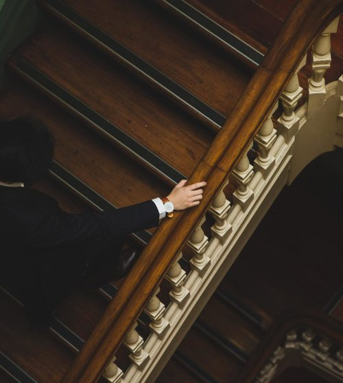 man walking up a large staircase with hand on the railing