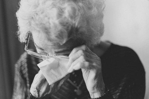 Elderly woman using tissue to wipe her eyes under her glasses