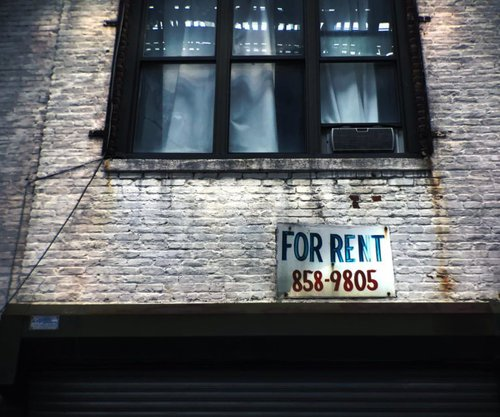 For rent sign outside brick building