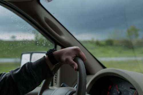 man with hand on steering wheel of car