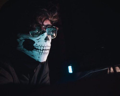 Man with skeleton mask and glasses driving