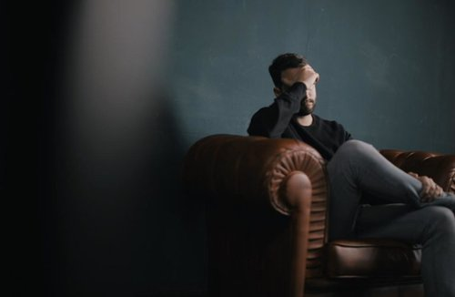 Man sitting on couch with hand on his face