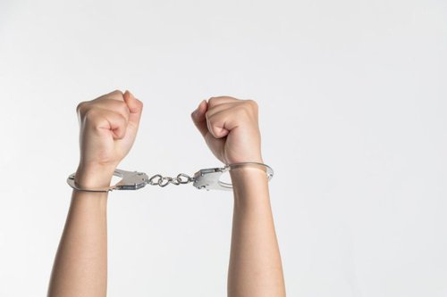 hands raised up making fists in handcuffs