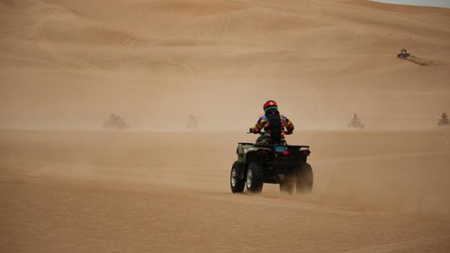 people riding atvs through sand