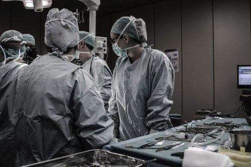 Five Surgeons standing in an operating room