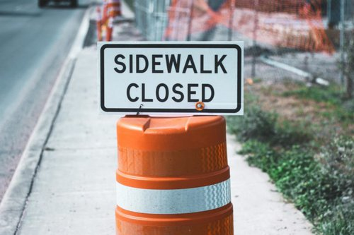 traffic cone with sign that says sidewalk closed