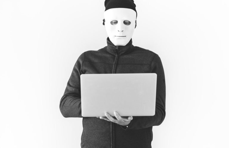 man in mask holding laptop