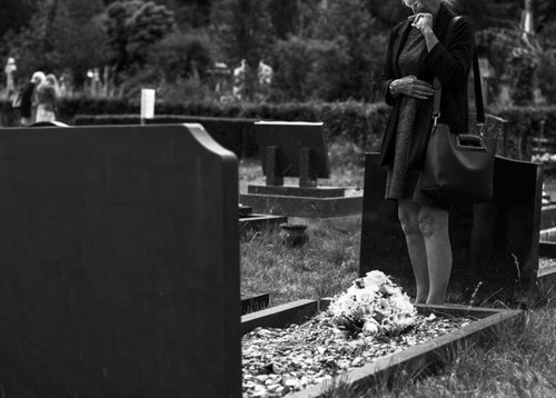 woman standing over grave with flowers on it