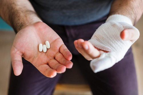 Man holding out his hands; one holding three pills and the other wrapped up for an injury