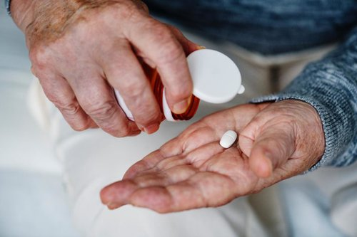 elderly man putting pill from container into his palm