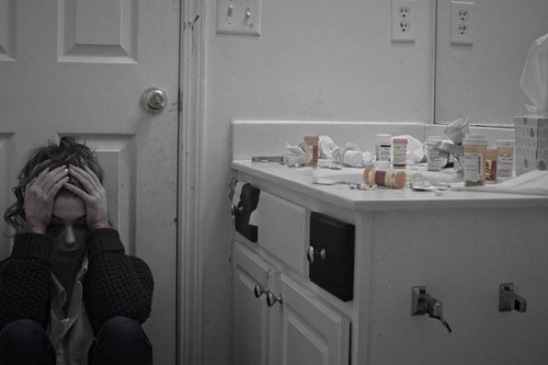 young woman on bathroom floor with her hands on her head and pill bottles on the bathroom counter