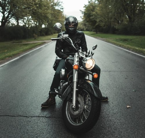 Man dressed in all black sitting on a motorcycle in the street