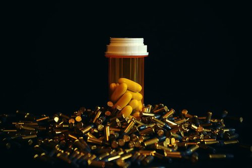 Bottle of pills surrounded by bullets