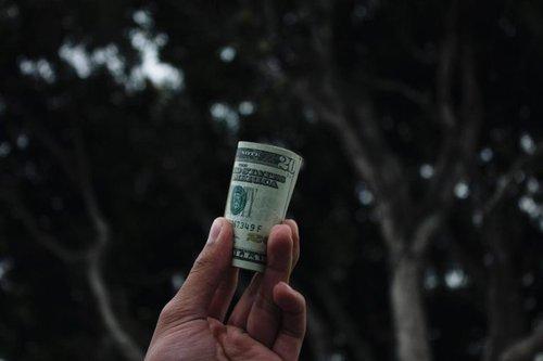 hand holding rolled up twenty dollar bills