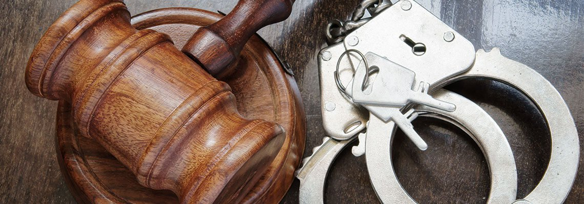 Wooden gavel next to handcuffs
