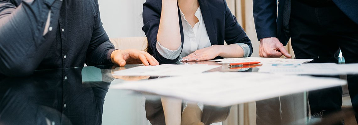 Man and woman sitting at table looking over divorce papers