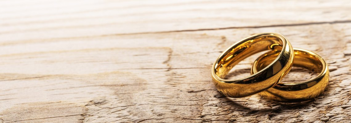 Two wedding rings sitting on a wooden surface