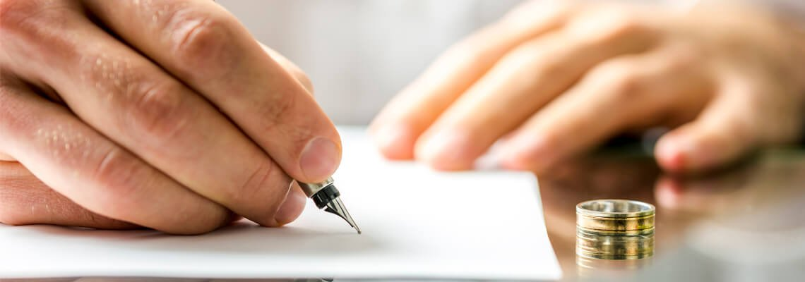 Person signing a document next to a wedding ring