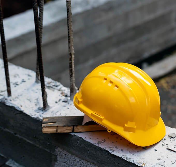 Hard hat resting on concrete near construction site