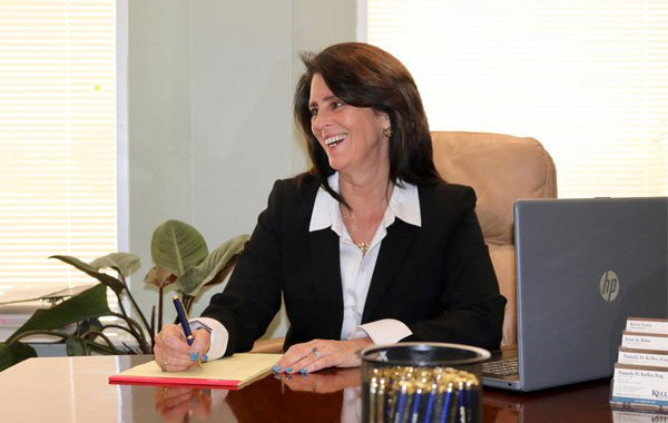 Attorney Pamela Keller Writing on Notepad at her desk