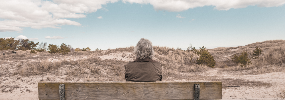 Elderly Woman Sitting on a Bench Looking into a Distance