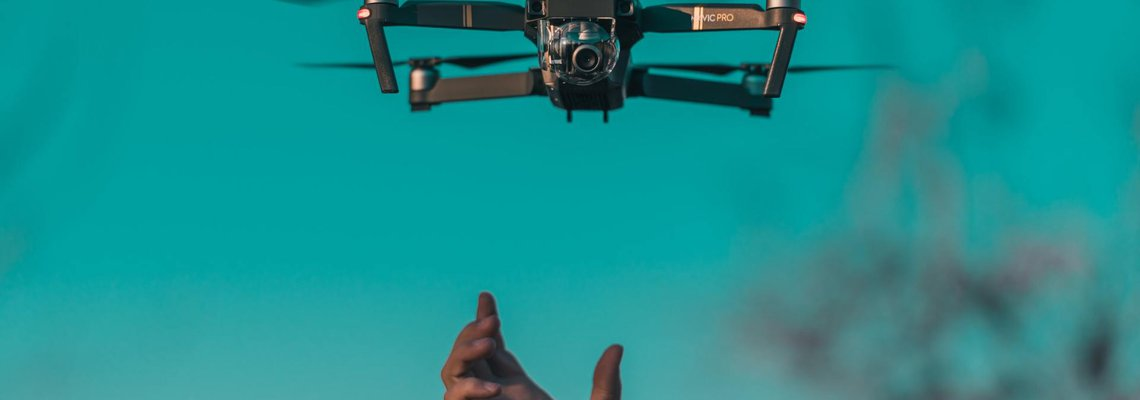 Hand reaching up for a drone