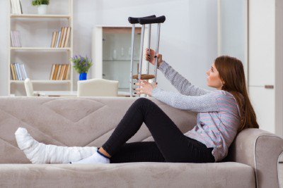 Woman lying on a couch wearing a cast and putting her crutches behind her