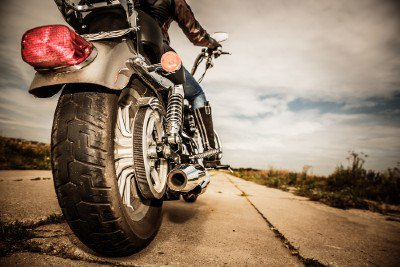 Motorcycle being ridden down a poorly paved road