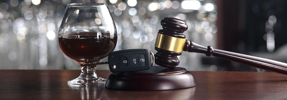 Glass of liquor next to keys and gavel on a bar