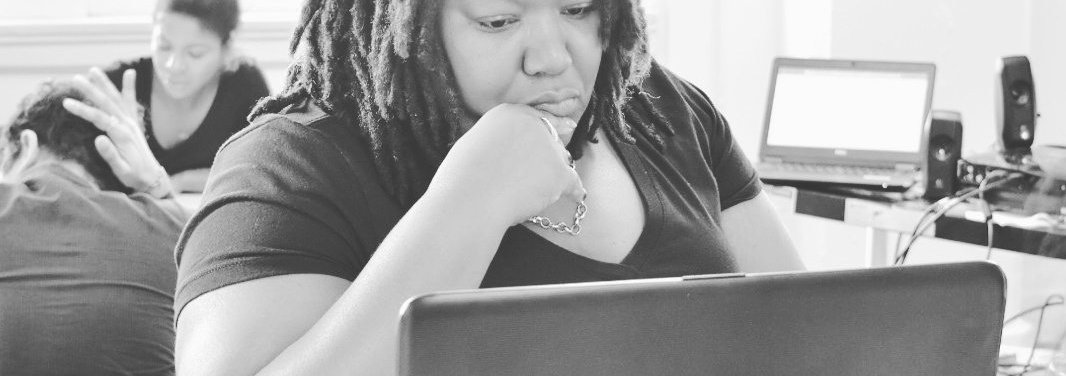 Canva - Grayscale Photo of Woman Wearing V-neck T-shirt Sitting in Front of Hp Laptop on Desk.jpg