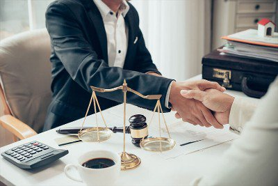 Two people shaking hands next to a cup of coffee and scales of justice