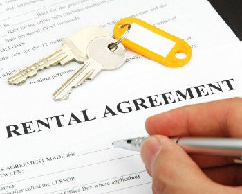 Rental agreement with keys on top being signed