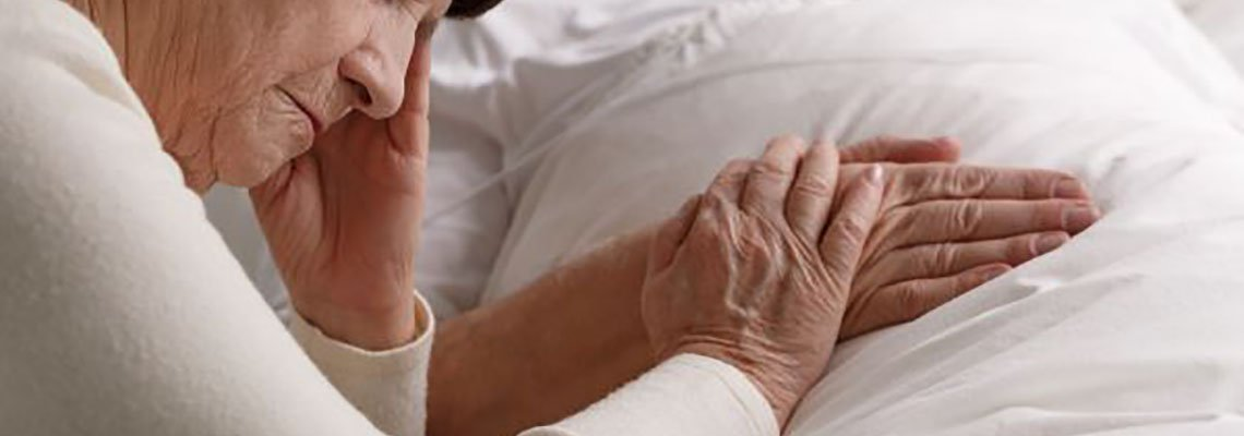 Woman holding her husband's hand in a hospital bed