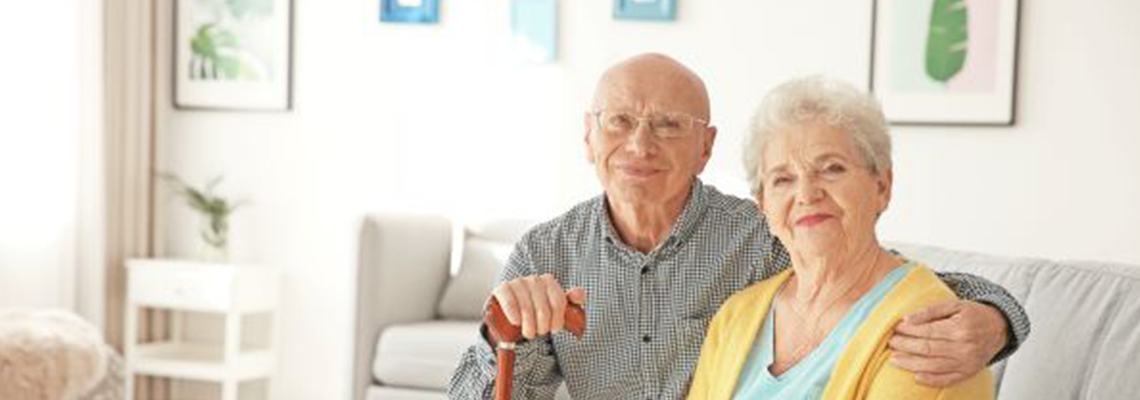 Older couple sitting on a couch smiling