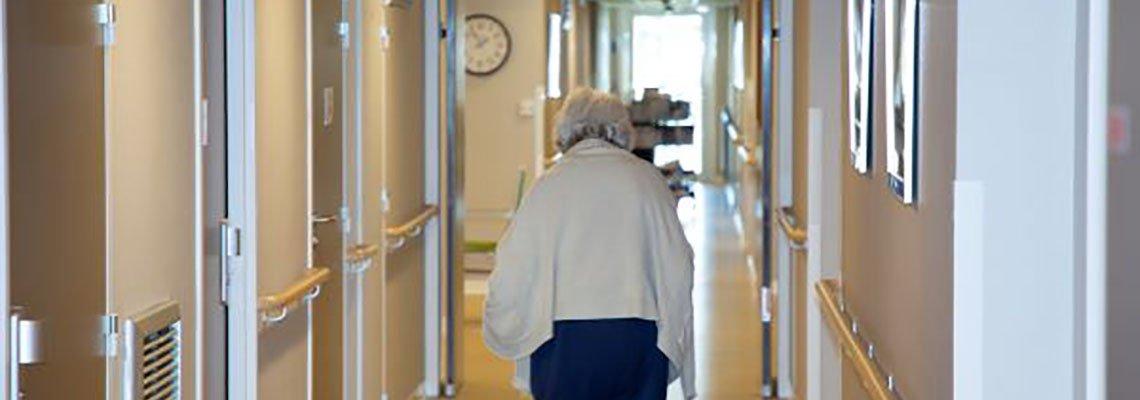 Elderly woman walking down a hallway