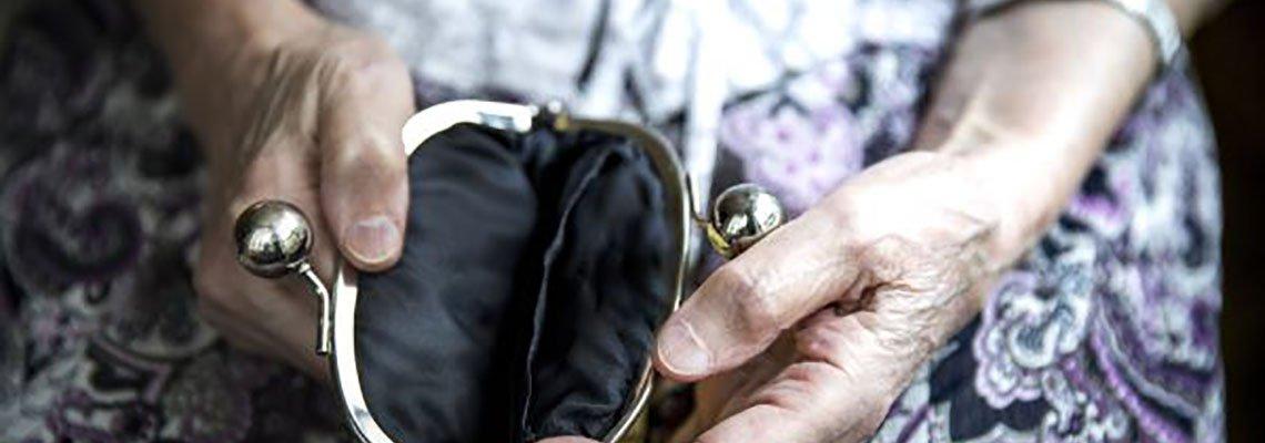 Elderly woman opening an empty coin purse