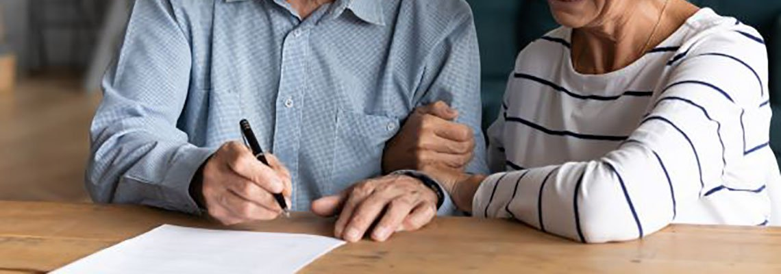 Elderly couple signing a prenup