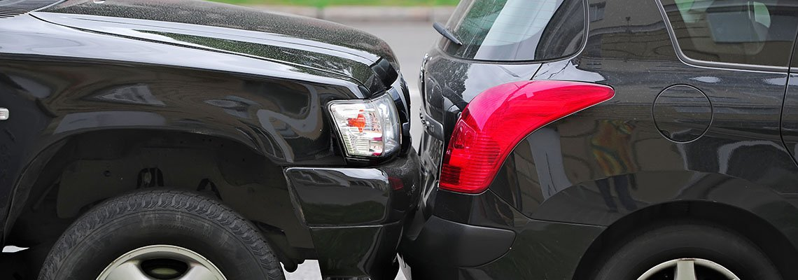 Truck hitting the bumper of a small car
