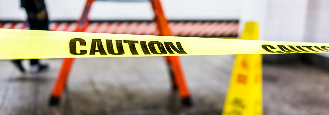 Caution tape marking off an icy surface near a caution cone