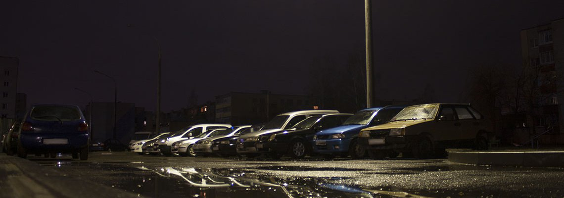 Dark parking lot lighting up a row of old cars