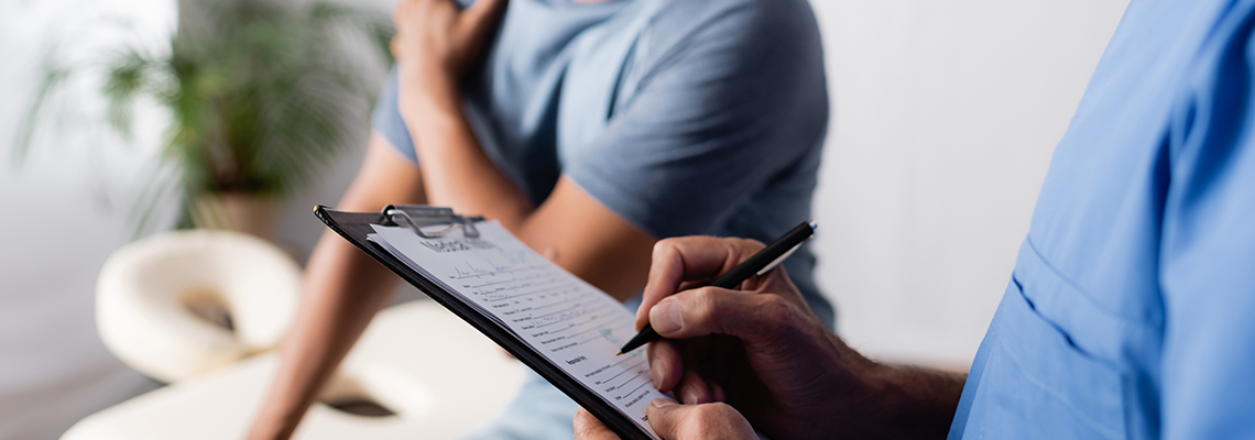 Man holding shoulder in a doctors office