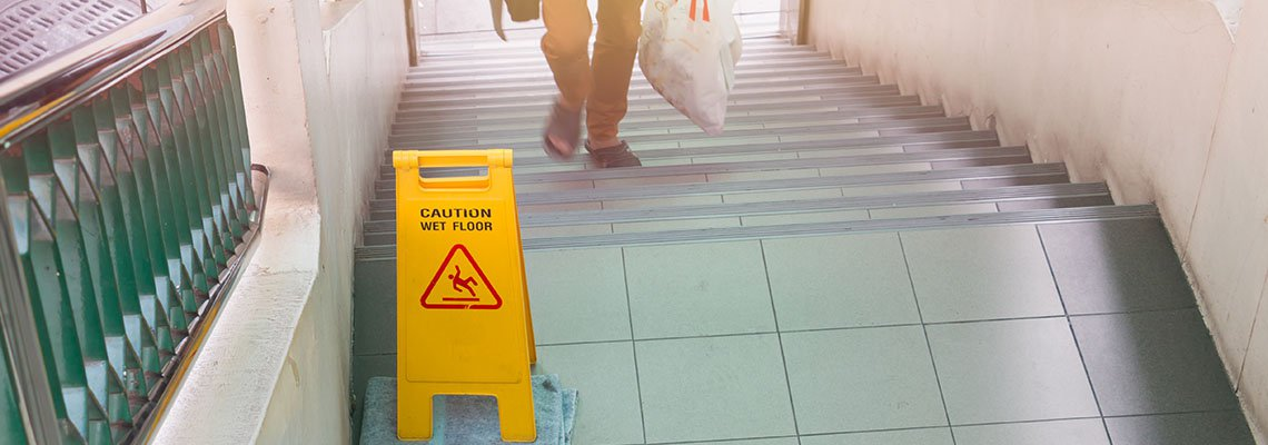 Caution wet floor sign on stairs with a man going up the stairs
