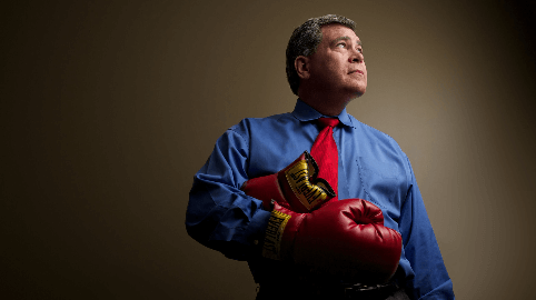 Attorney Ralph Martinez in dress clothes and boxing gloves