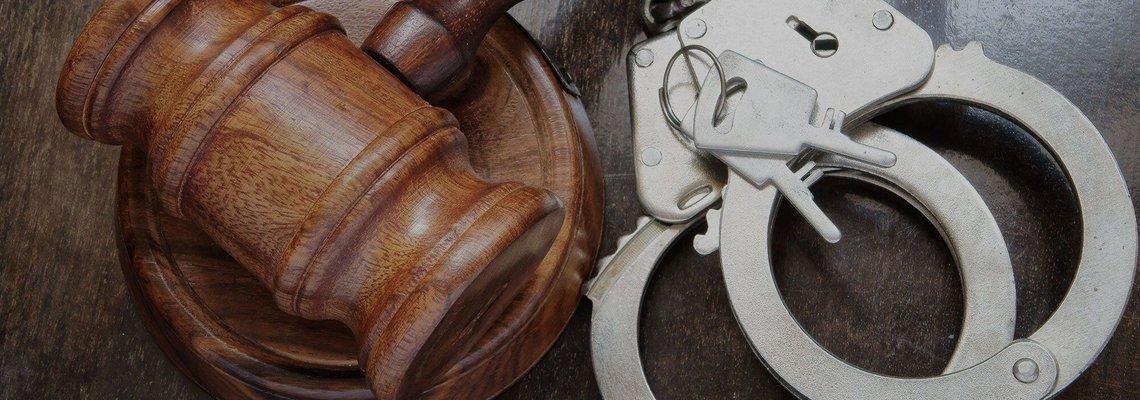 wooden gavel next to handcuffs