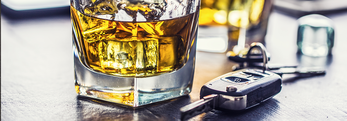Car keys and glass of alcohol